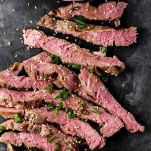 Sous vide skirt steak thinly sliced and garnished with chopped green onion.