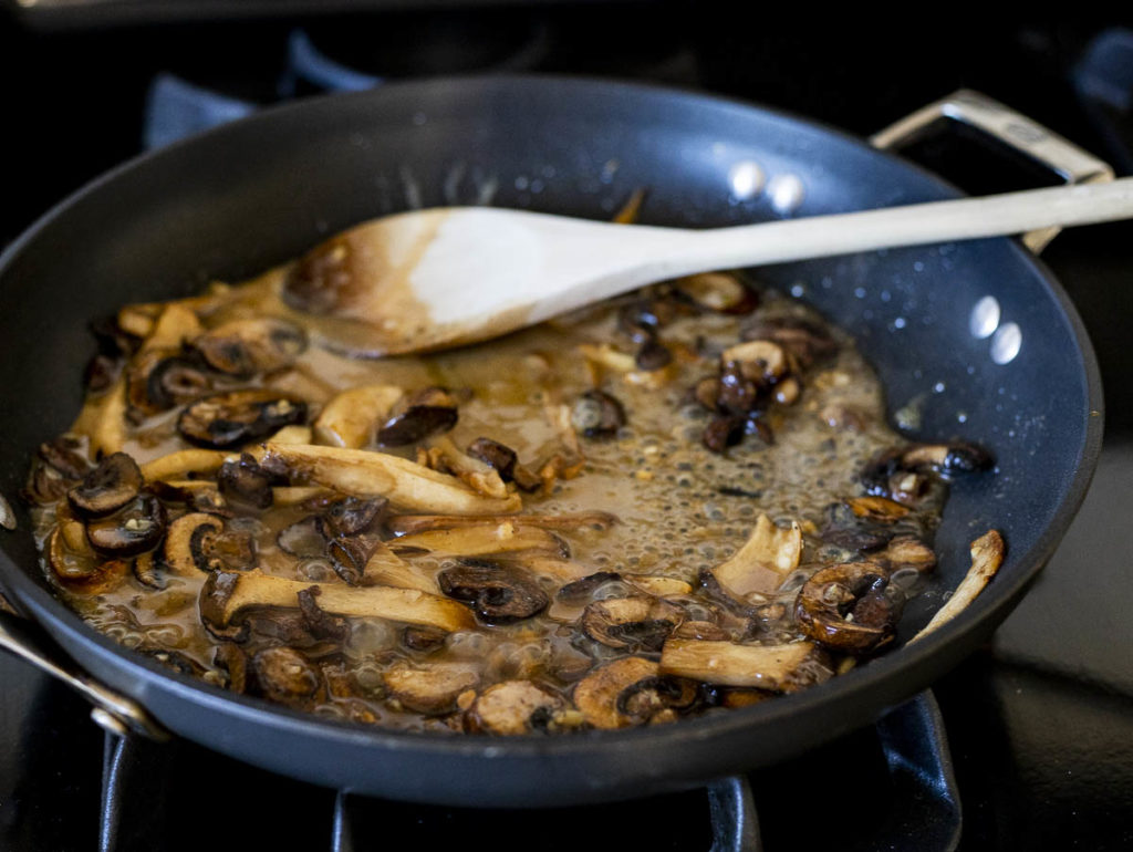 mushrooms cooking in a skillet with liquid
