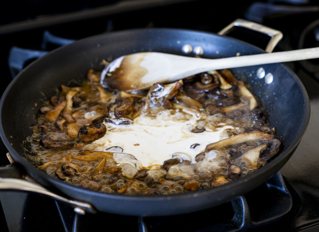 mushrooms cooking in a skillet with liquid and cream
