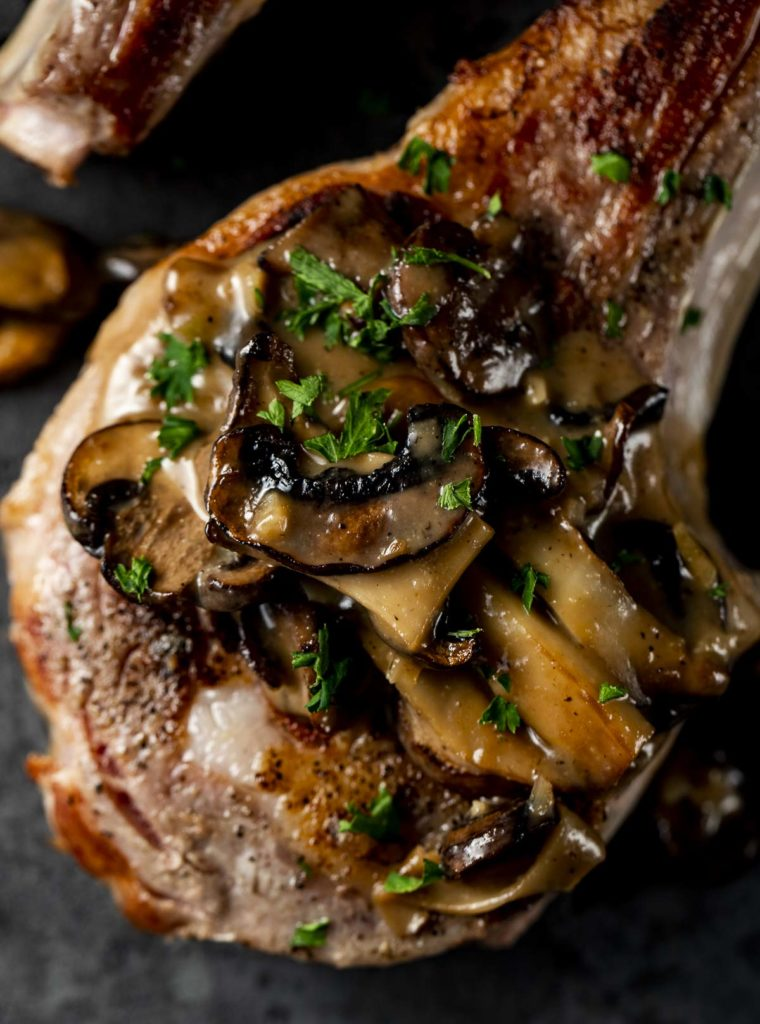 a veal chop smothered in mushroom sauce and parsley