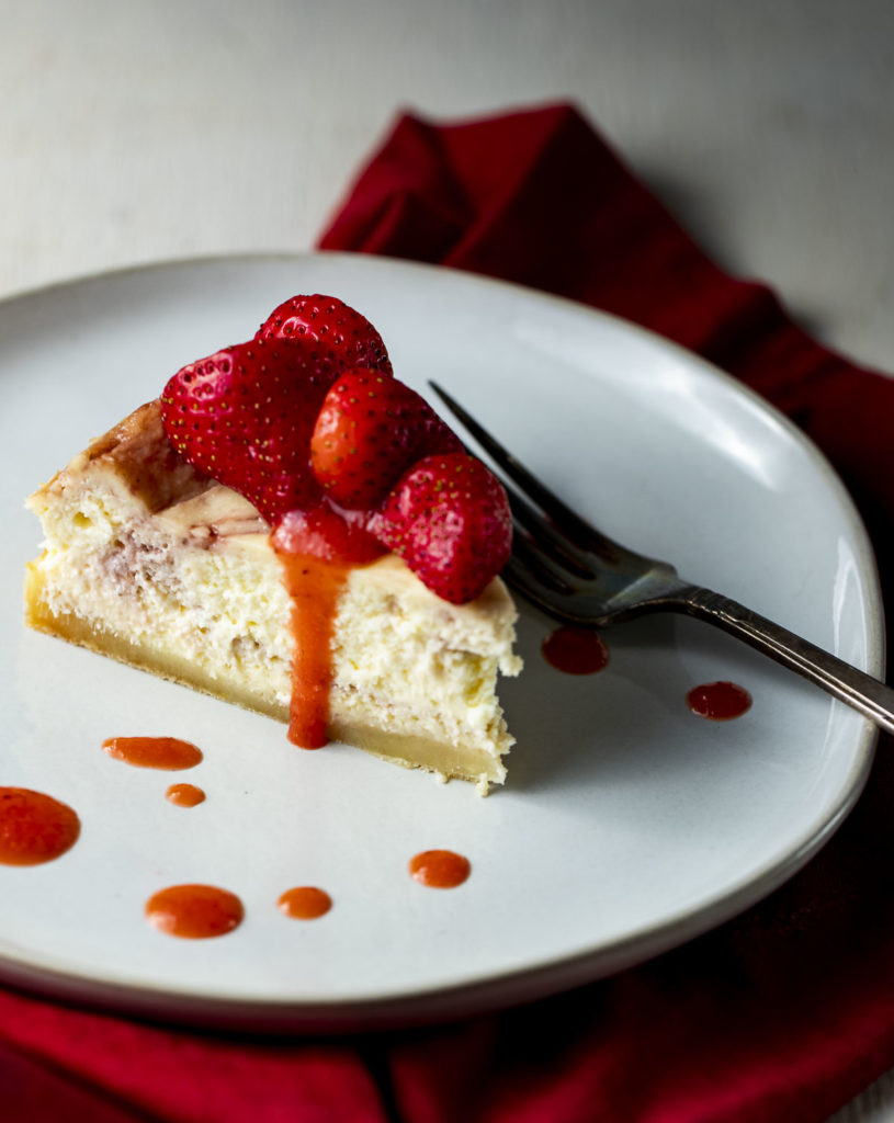 a piece of cheesecake on a plate drizzled with fresh strawberries