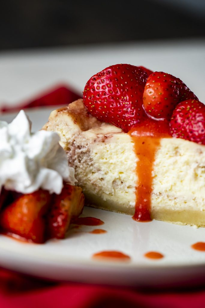 strawberries drizzling down the side of a piece of cheesecake