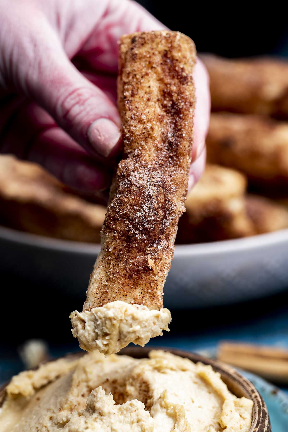 Churros being dipped into a caramel cheesecake dip.