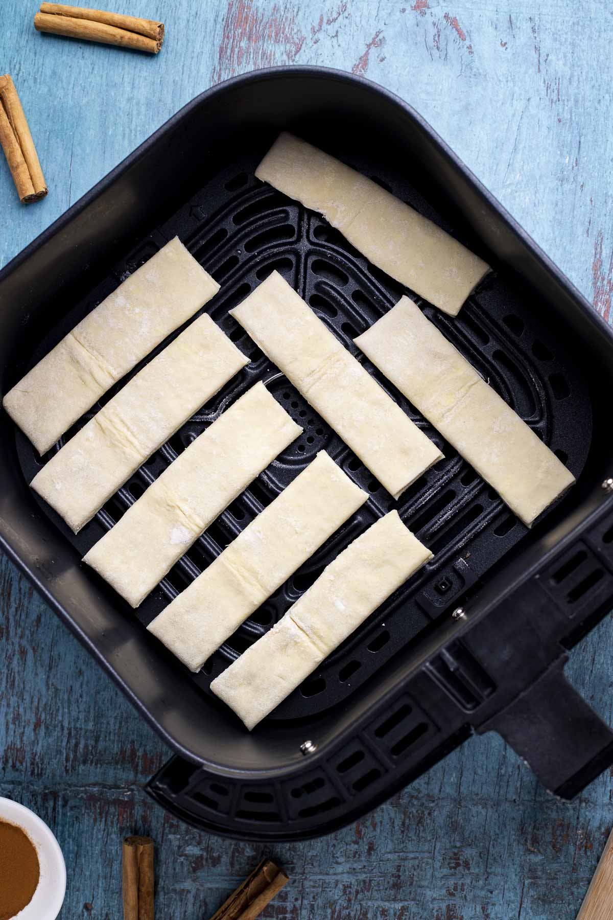 Puff pastry strips added into an air fryer basket.