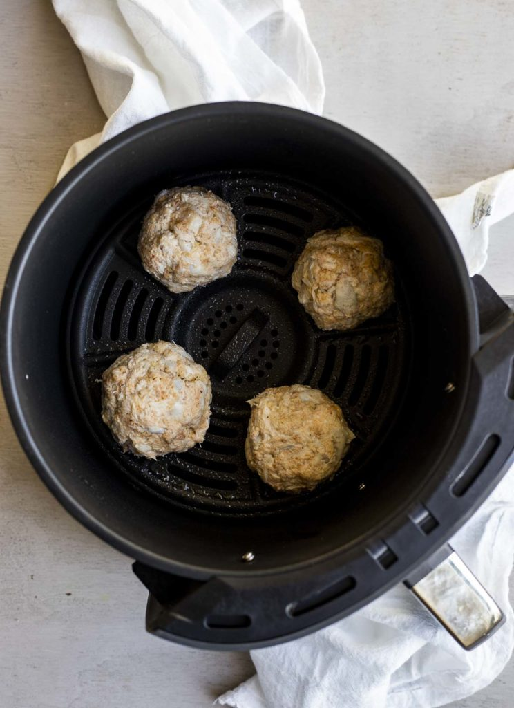 Overhead view of four crab cakes inside of an air fryer basket.