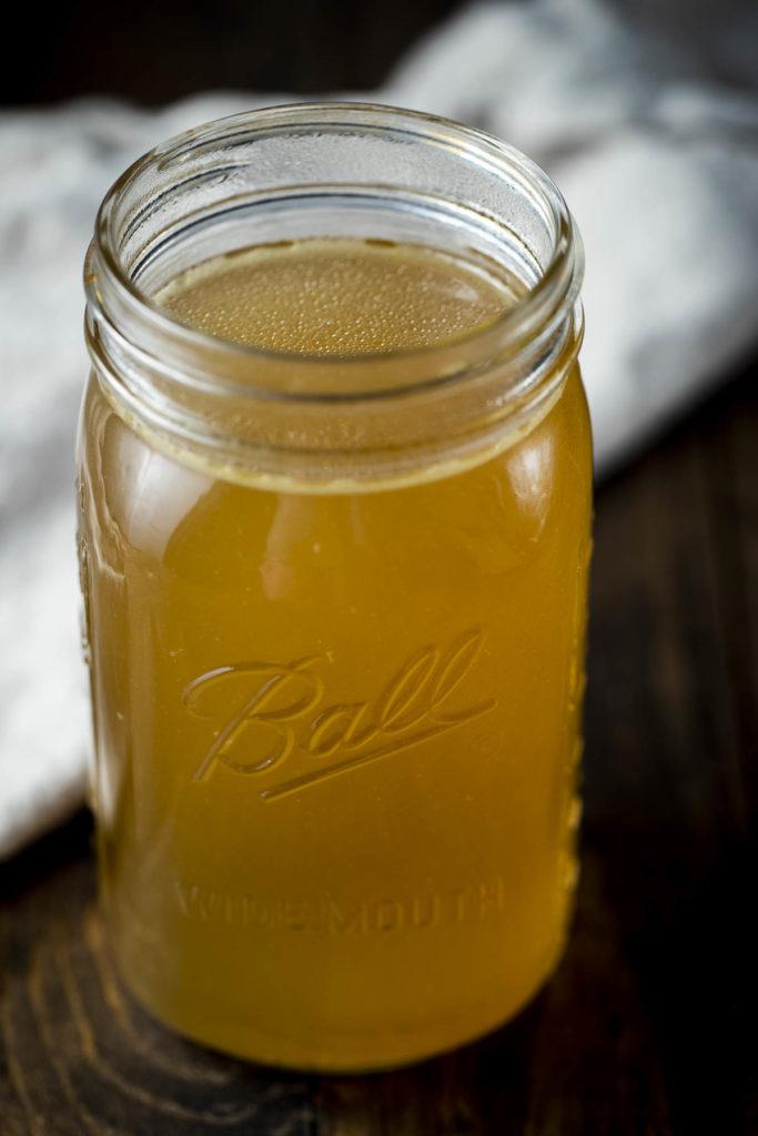 a glass jar of golden liquid
