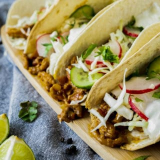 Set of four lamb tacos with garnishes.