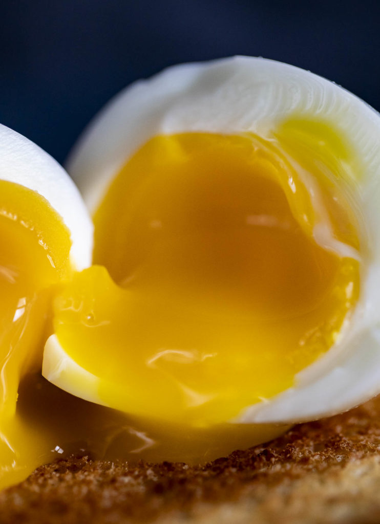 soft boiled egg cut in half with yolk running out