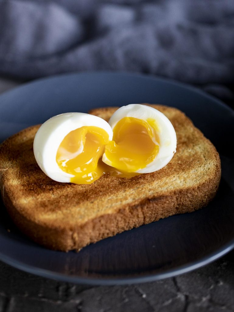 a halved soft boiled egg with runny yolk on toast