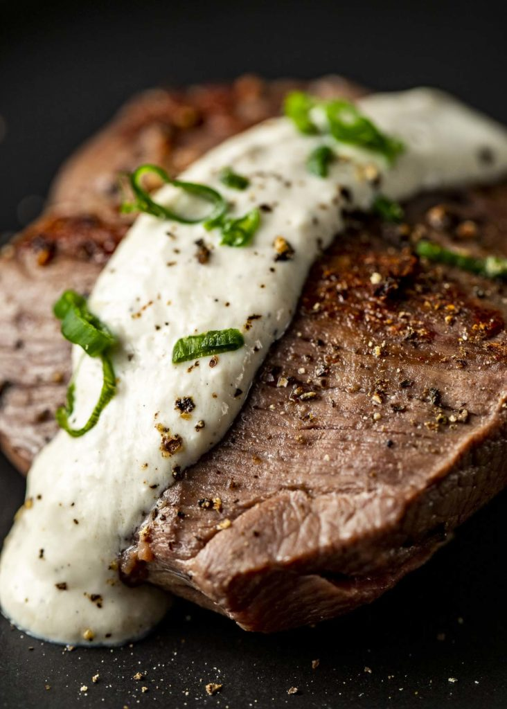 a seared pirce of beef with white sauce and chives on top
