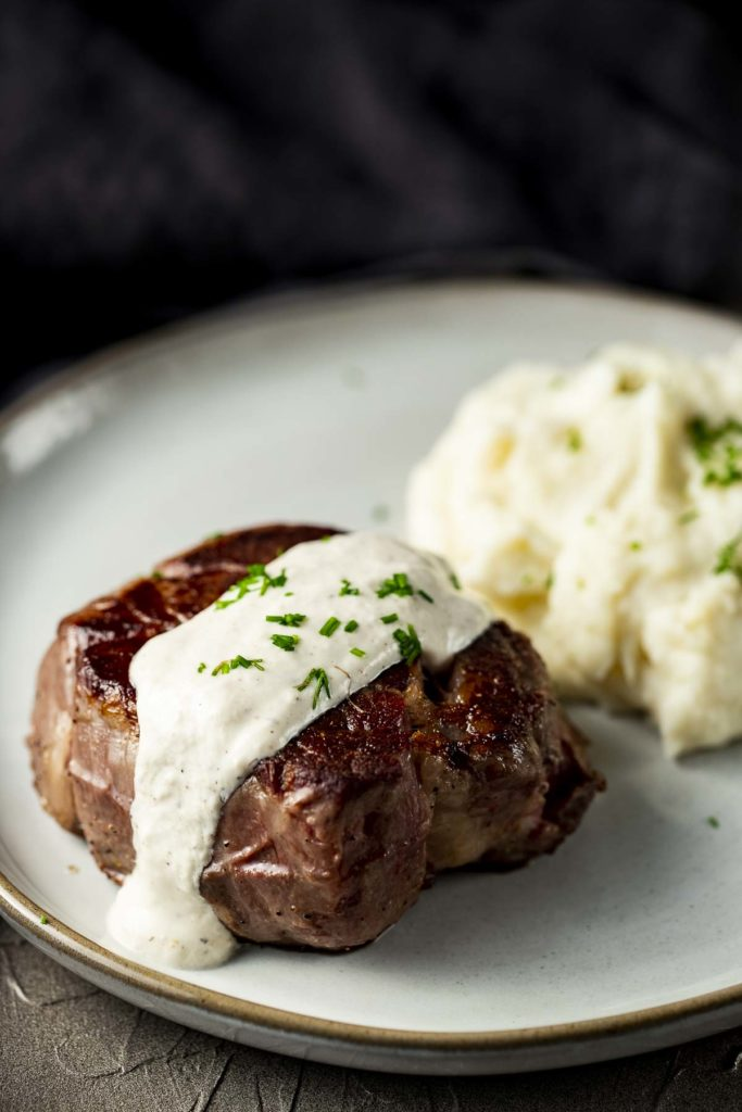filet mignon on a plate with mashed potatoes and white sauce