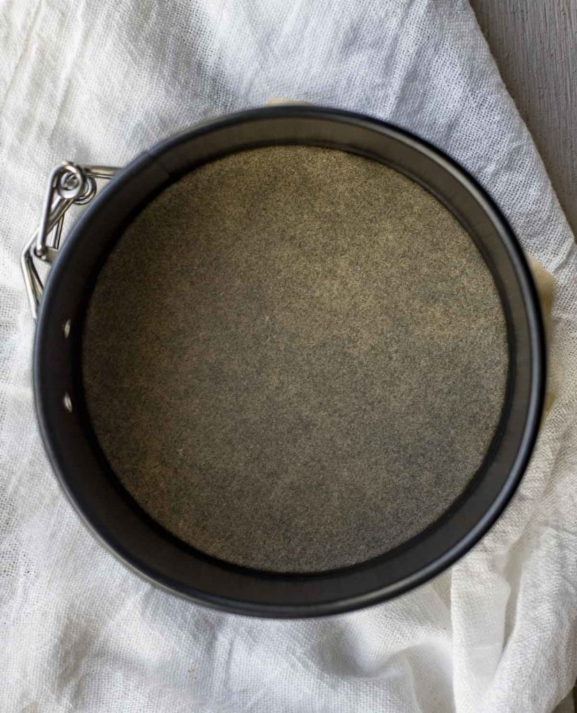 Lining a spring form pans with parchment paper.
