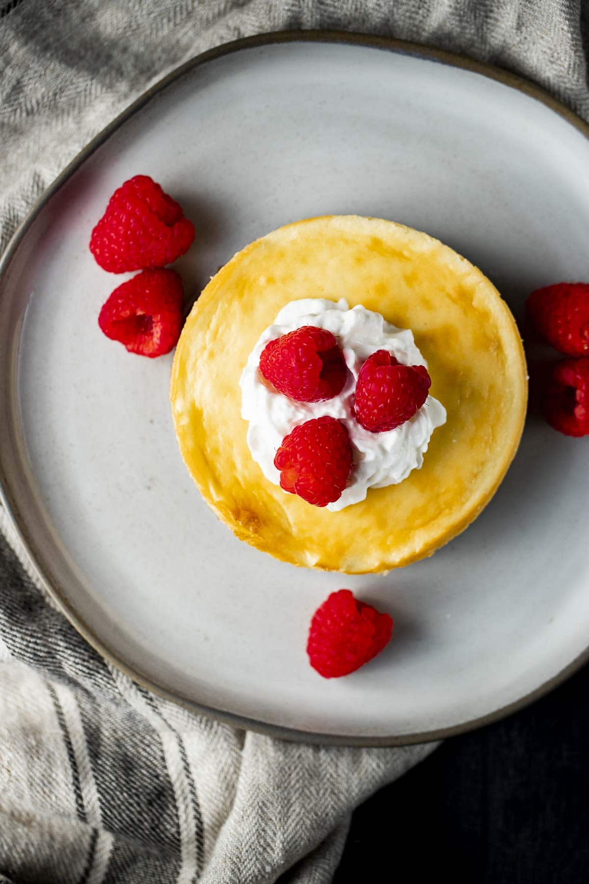 Overhead view of a cheesecake made in an air fryer with whipped cream and raspberries on top.