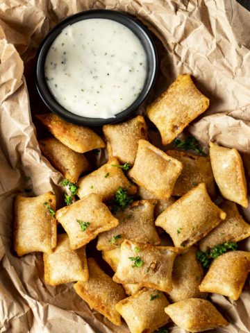 Overhead view of pizza rolls from the air fryer beside ranch dipping sauce.