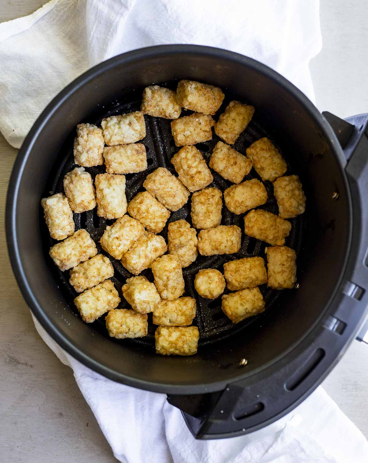 Tater tots in the air fryer before frying.