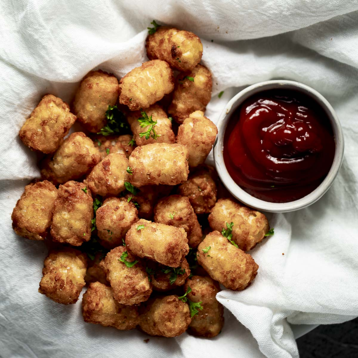 Air fryer tater tots beside a serving of ketchup.