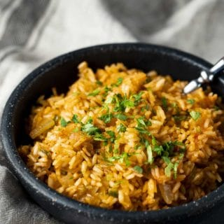 A bowl of Spanish rice with a spoon inserted.