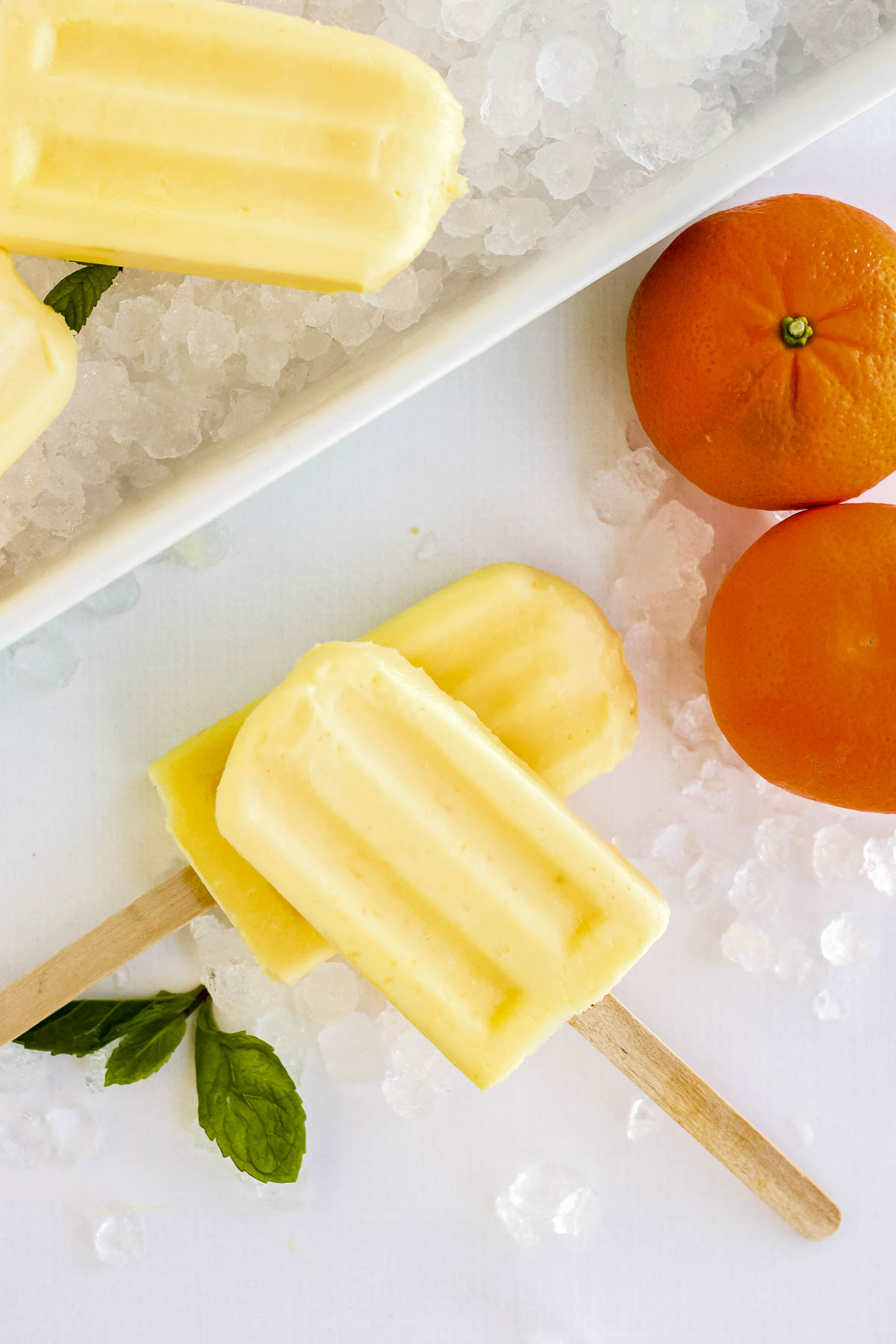 Two orange popsicles stacked on top of each other.