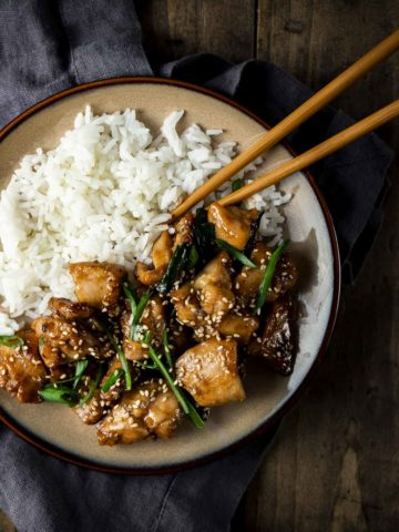 A plate with rice, shanghai chicken, and green onions with a pair of chopsticks.