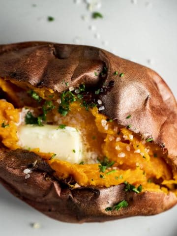 An air fryer sweet potato on a plate with melting butter on top.