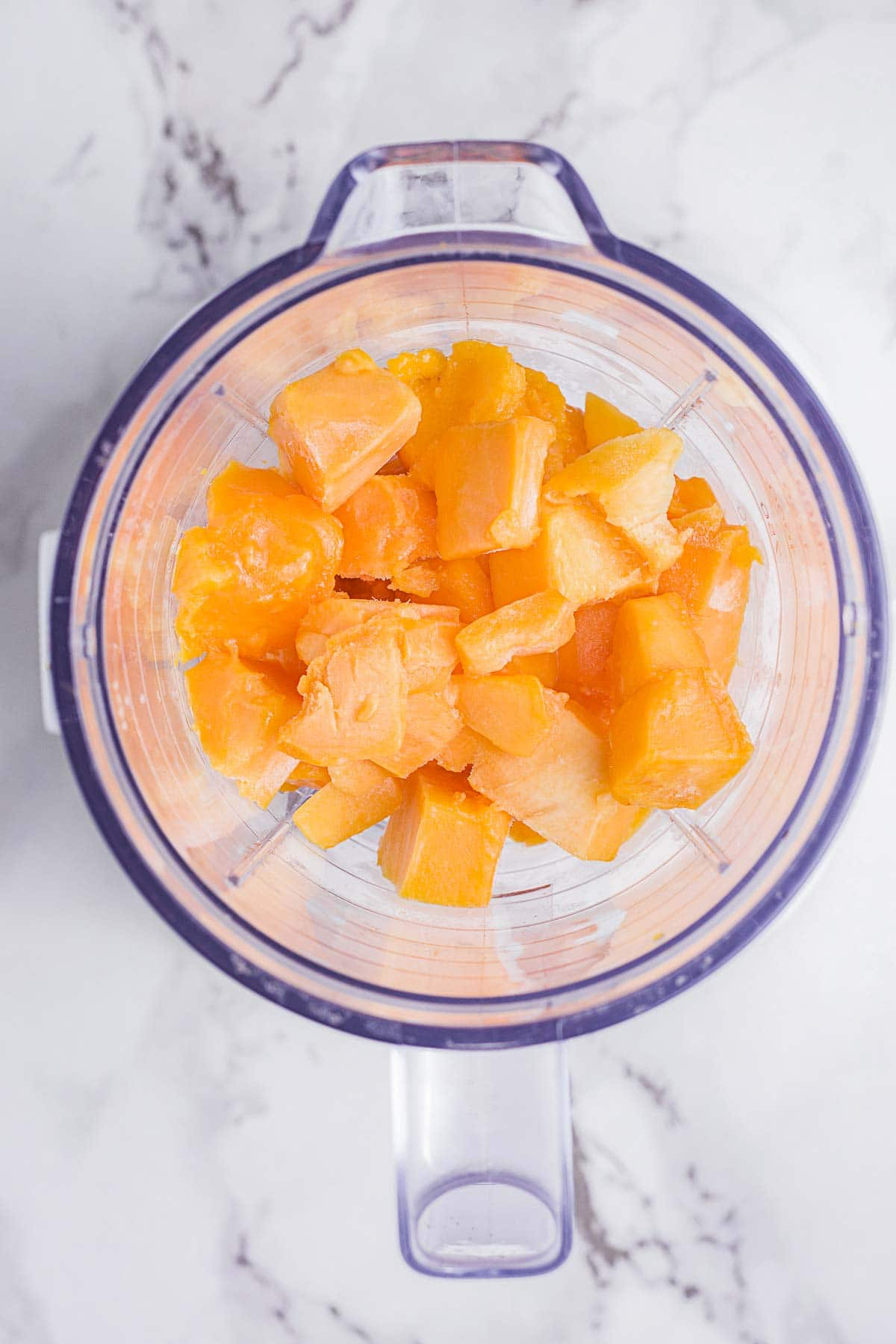 Diced mango added to a blender.