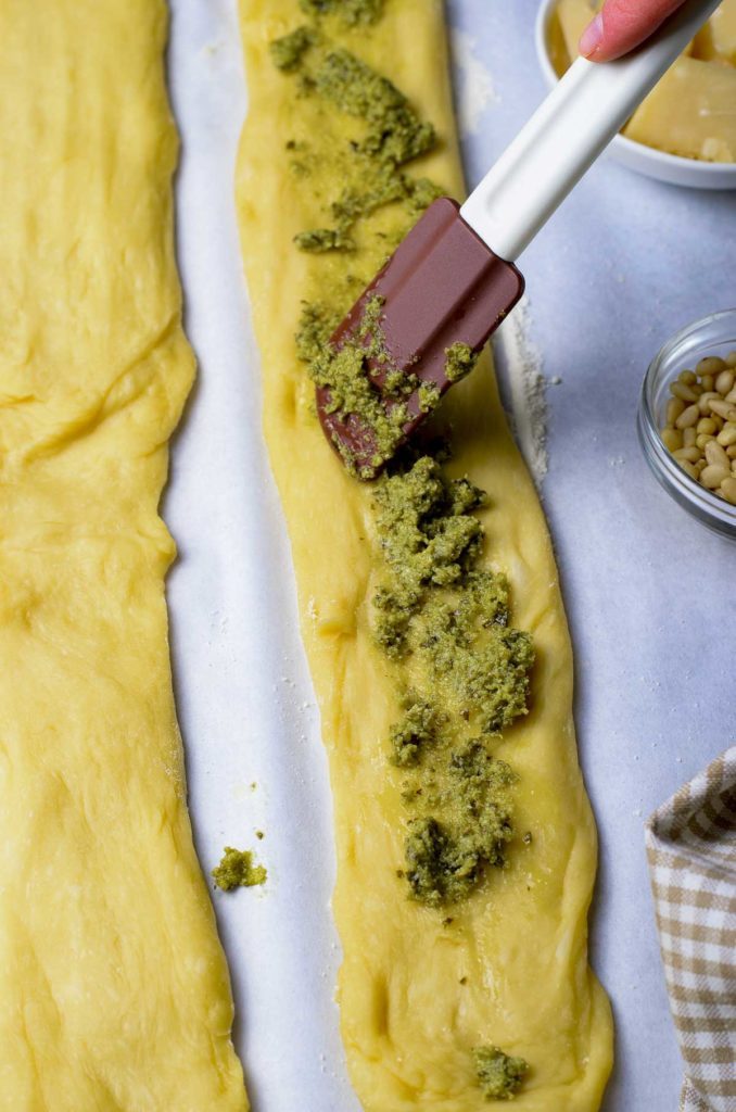Spreading pesto onto the rolled dough with a spatula.