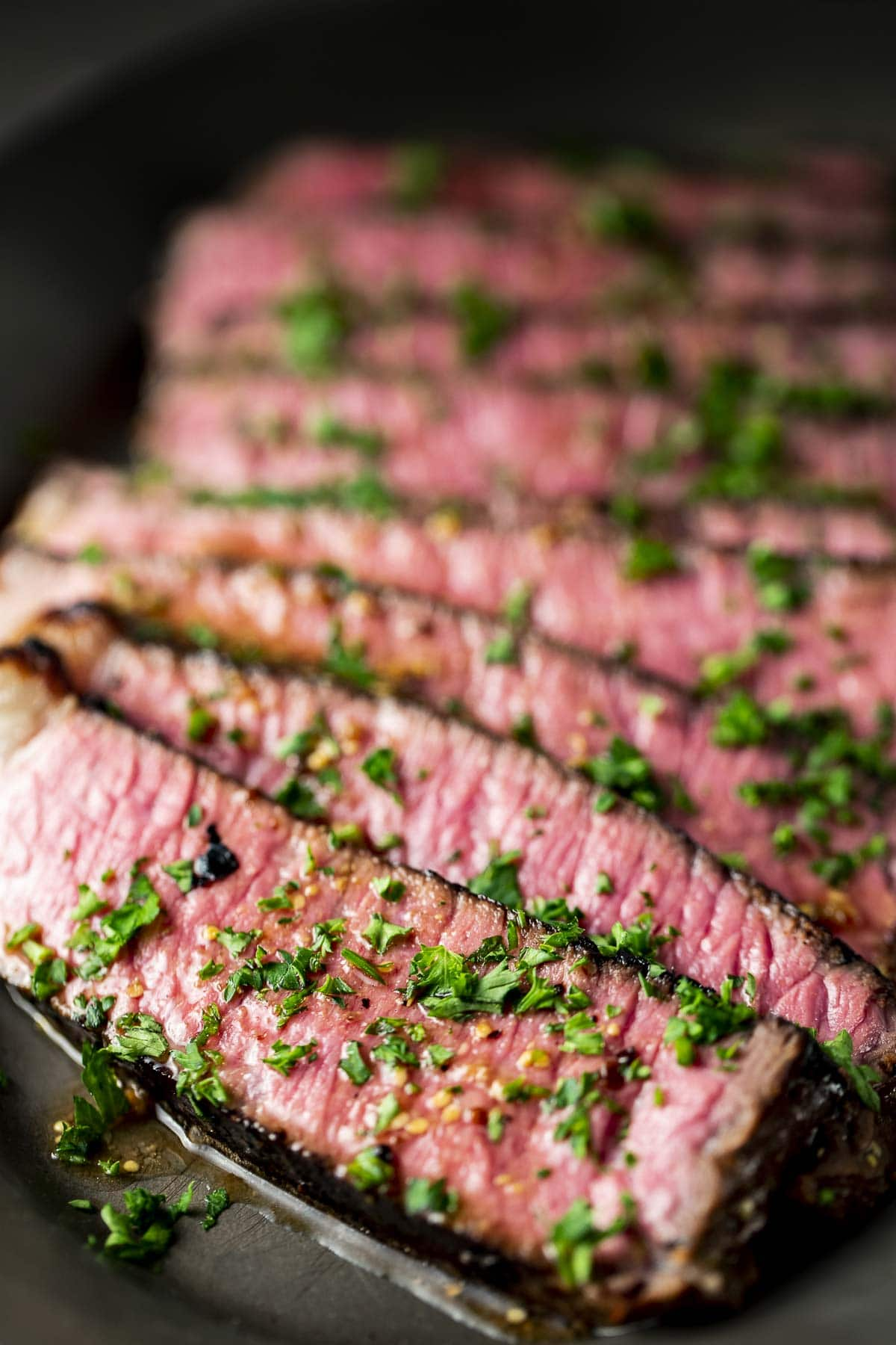 Steak cut across the grain and topped with chopped herbs.