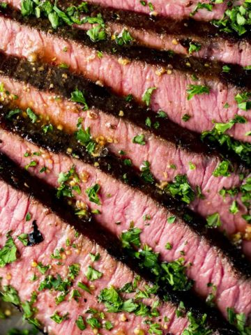 Close up of a London broil sliced and garnished with herbs.
