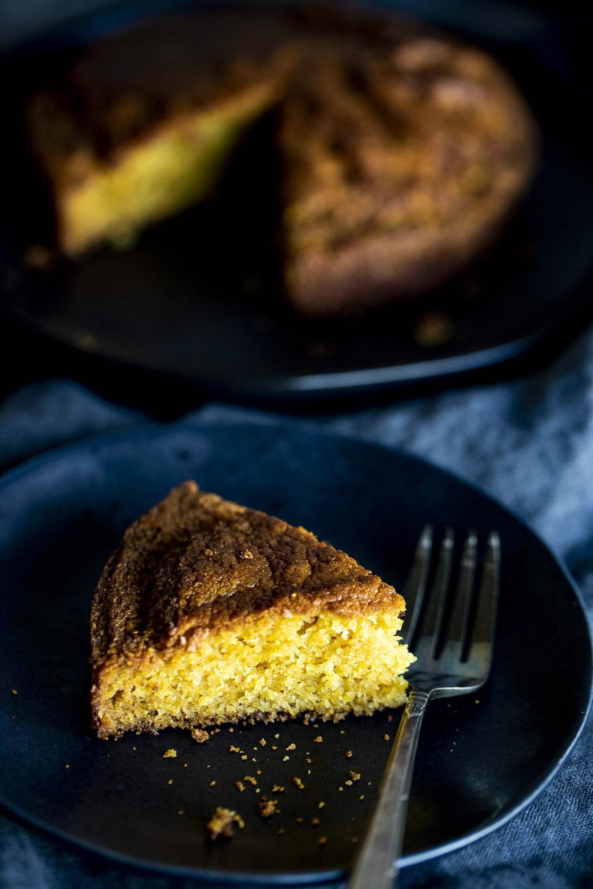 A slice of cornbread on a black plate with a fork.