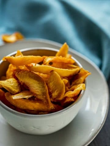 Dehydrated peach slices in a white bowl on a white plate.