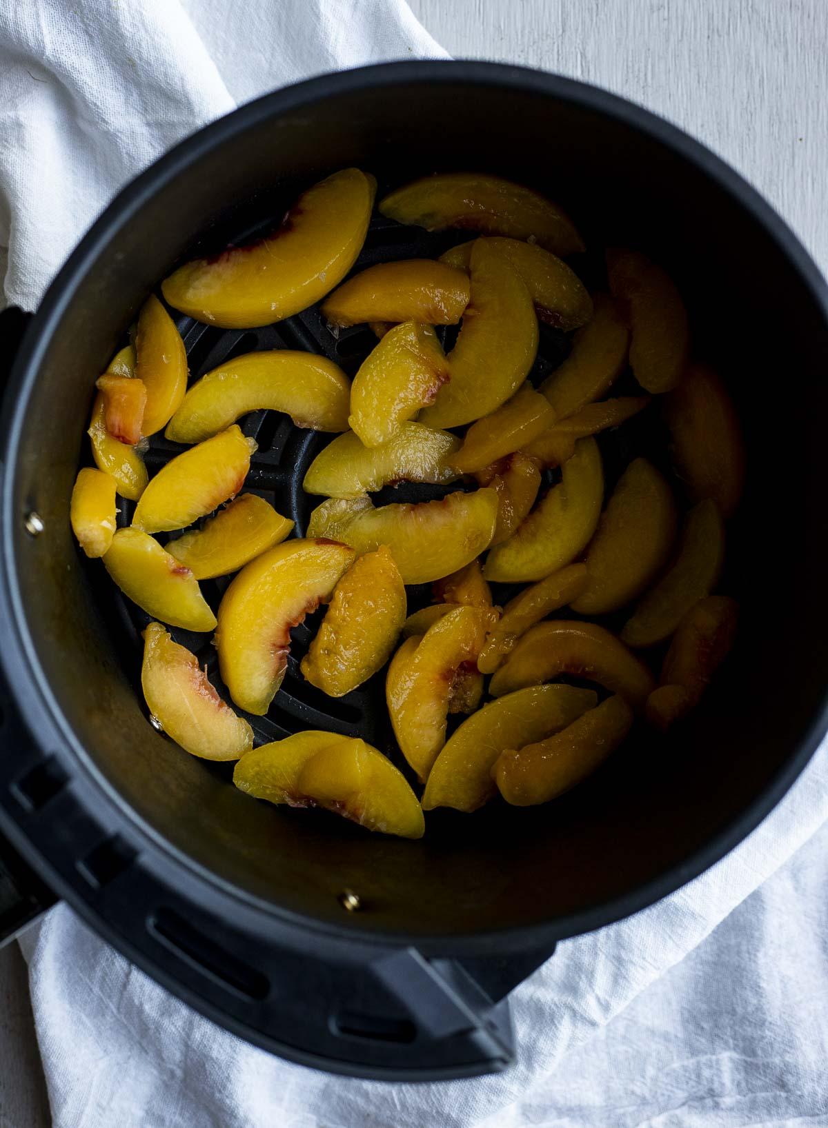 Peach slices arranged in a single layer in an air fryer basket.