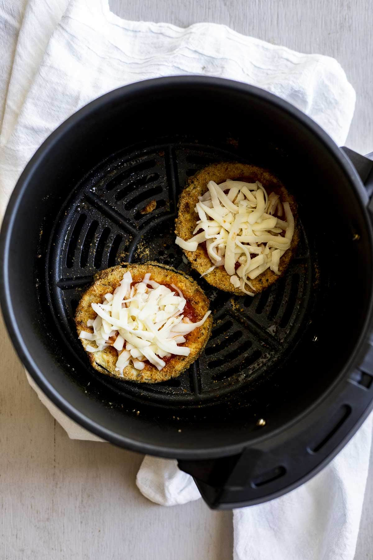 Two slices of eggplant in an air fryer basket and topped with marinara and cheese.