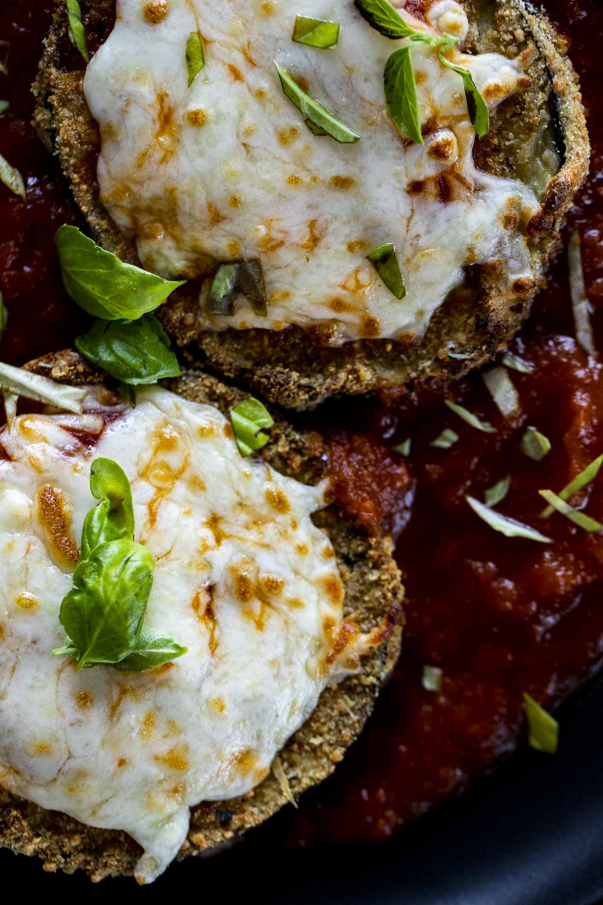 Close up of eggplant parmesan with melted mozzarella on top.