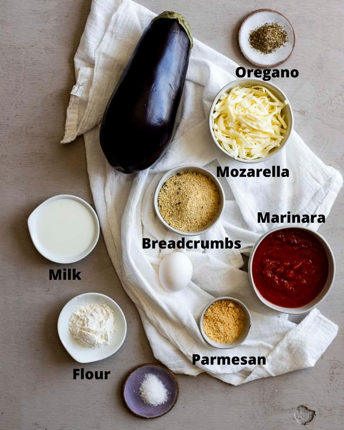 Ingredients to make air fryer eggplant parmesan arranged individually and labelled.