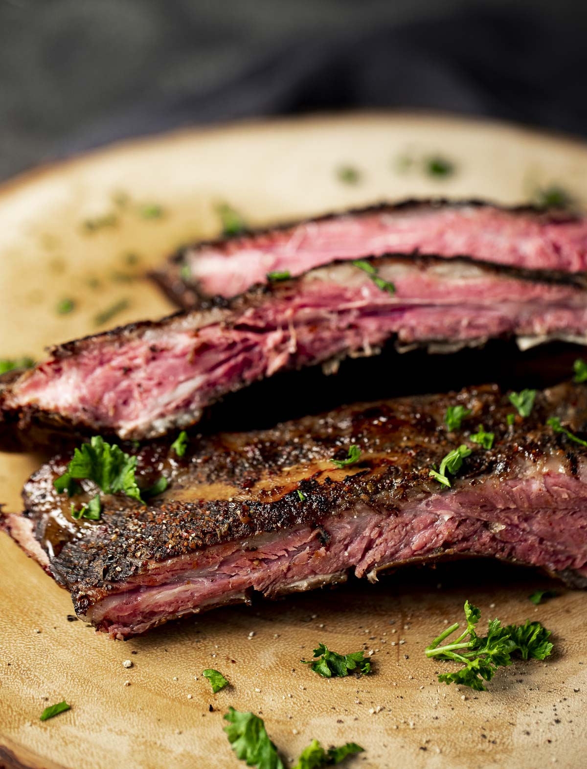 Beef back ribs cooked, sliced and arranged on a wooden board.