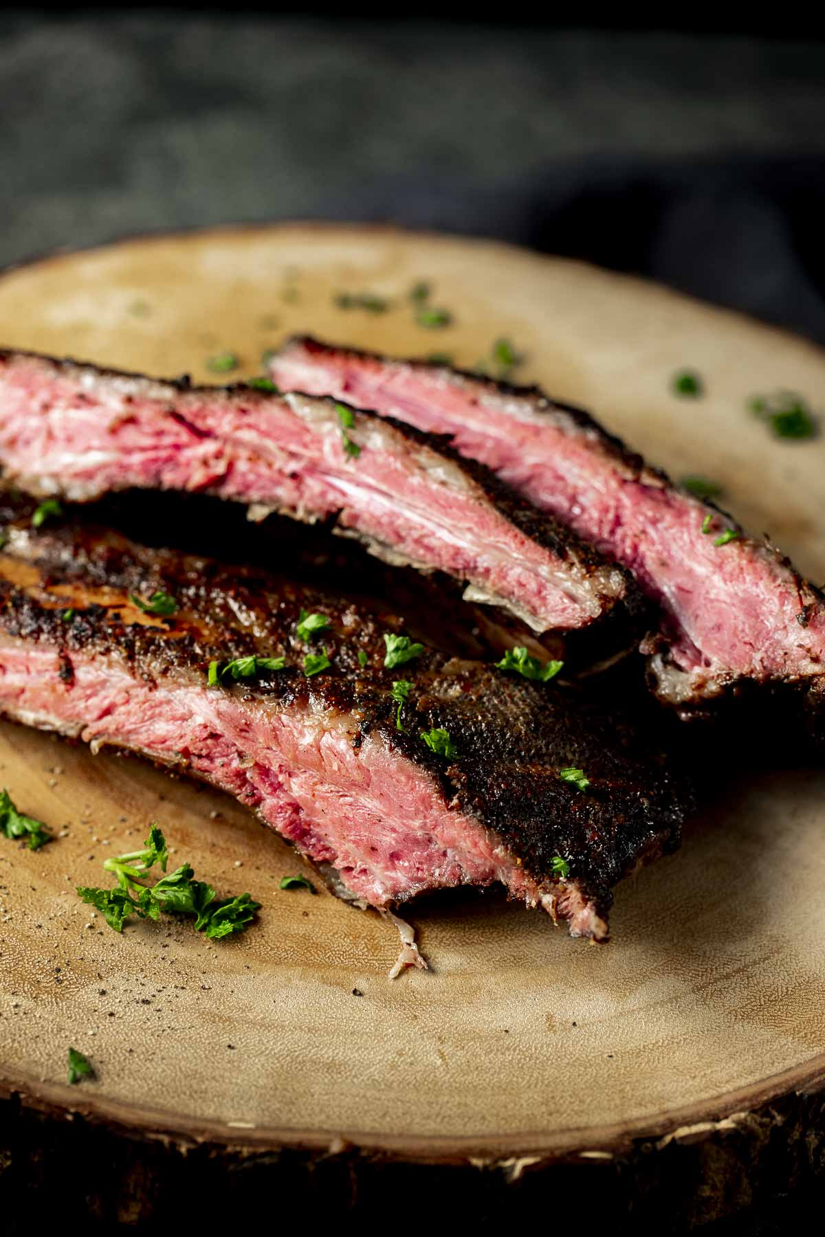 Beef ribs cut into slices and arranged on a wooden board.