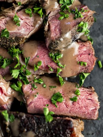 Up close view of slices of chuck roast topped with gravy and chopped herbs.