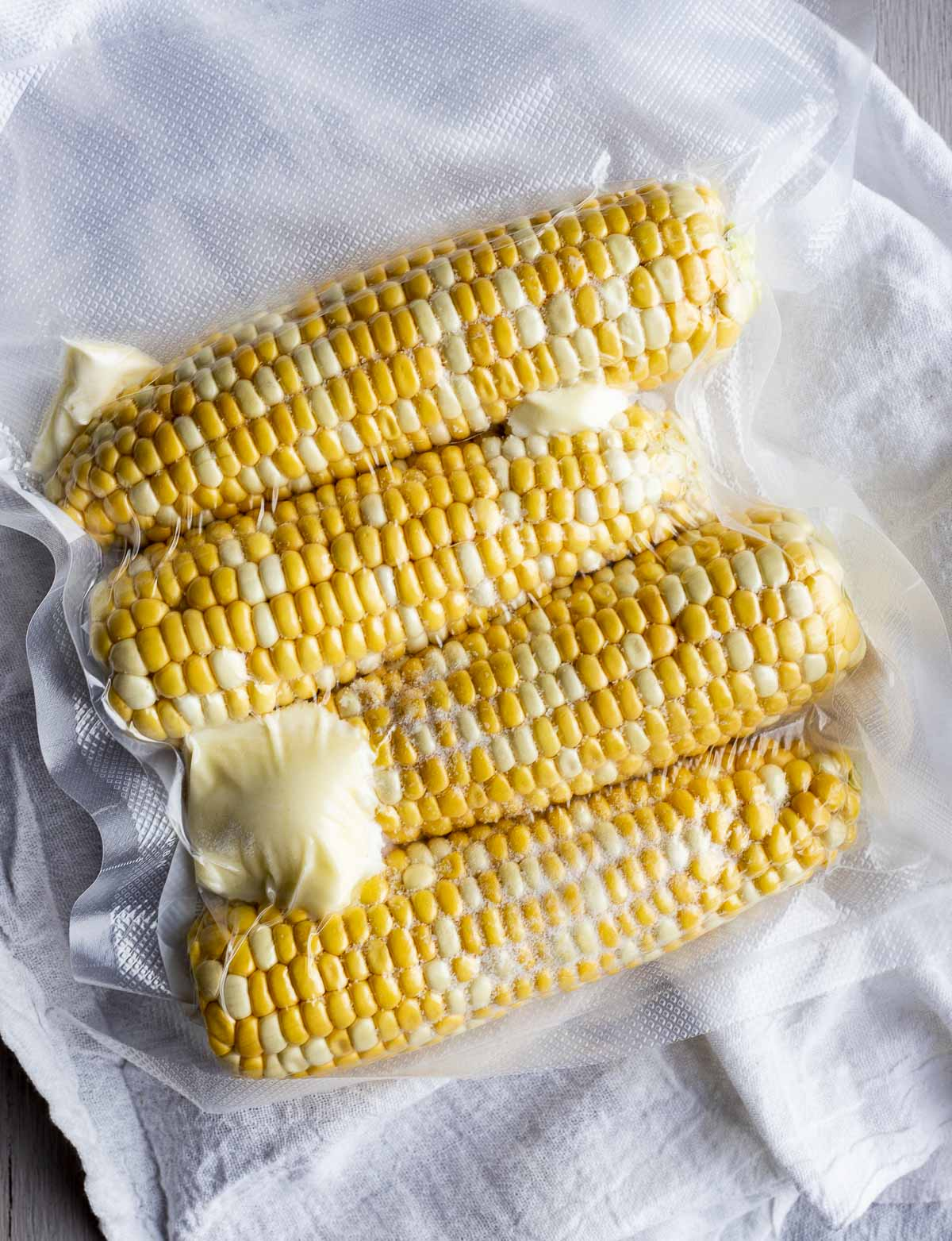 Four ears of fresh corn vacuum sealed in a bag with butter.