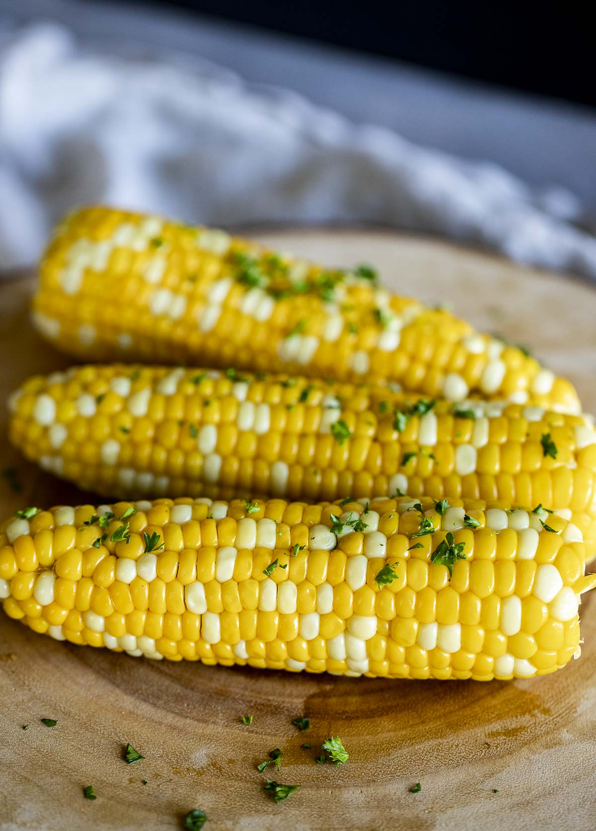 Side view of cooked corn topped with chopped fresh herbs.