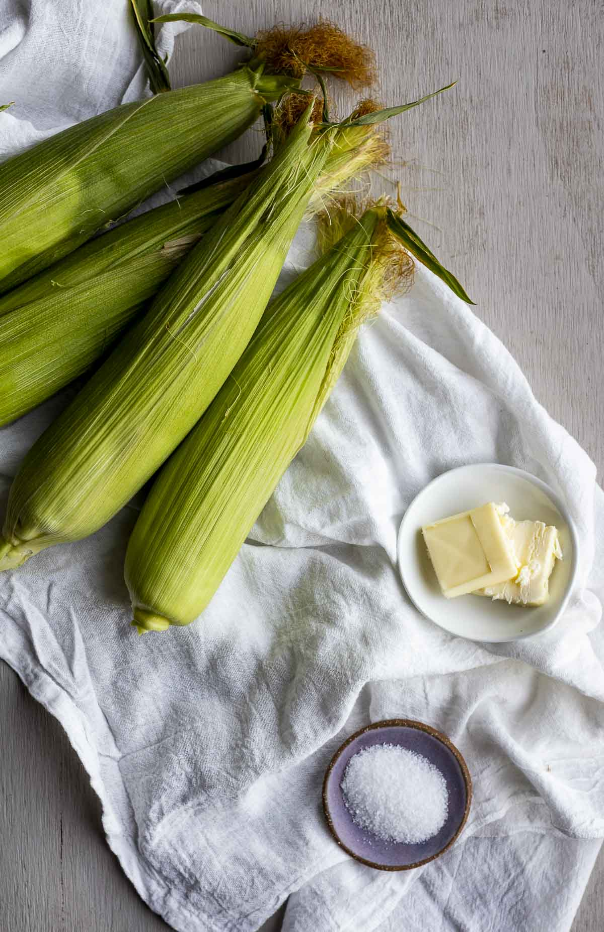 Four ears of corn in their husks, slices of butter and salt arranged individually on a white cloth.
