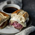 French dip sandwich on a plate with a bowl of jus.