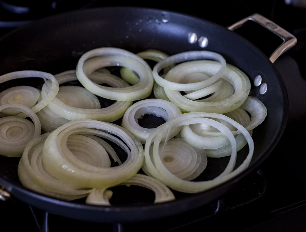 Onions being sauteed in a skillet.