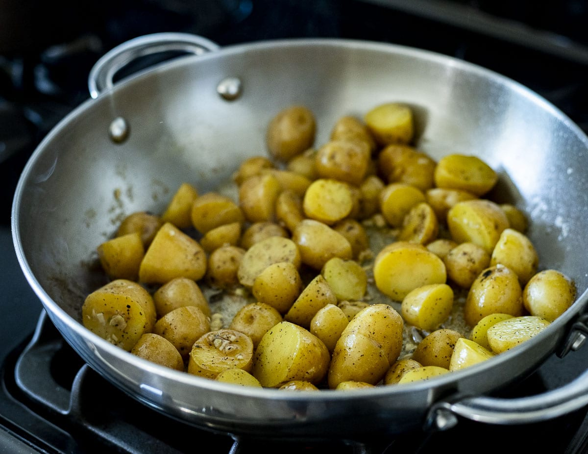 Mini potatoes being browned in a skillet.