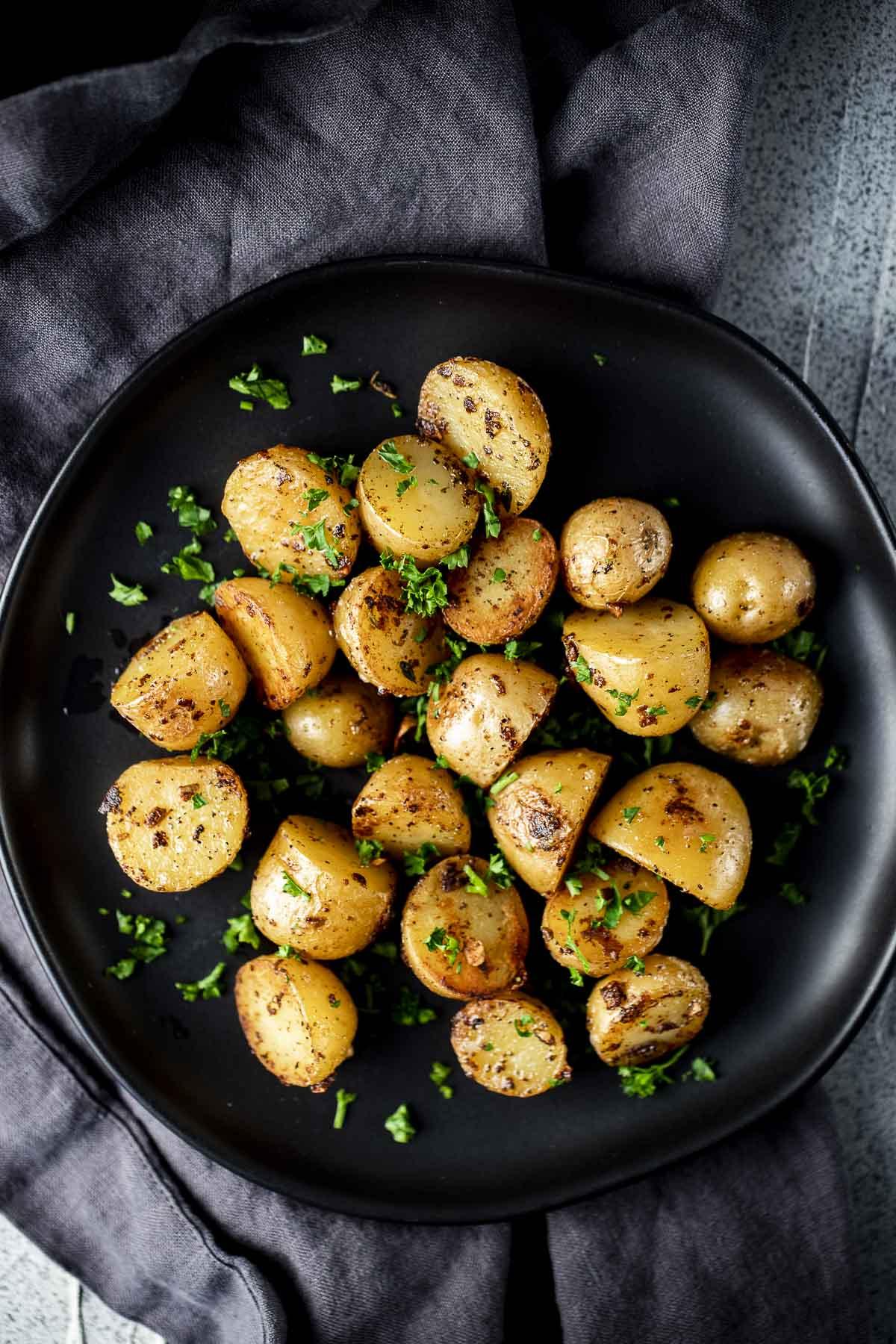 Overhead of mini sous vide potatoes arranged on a black plate.