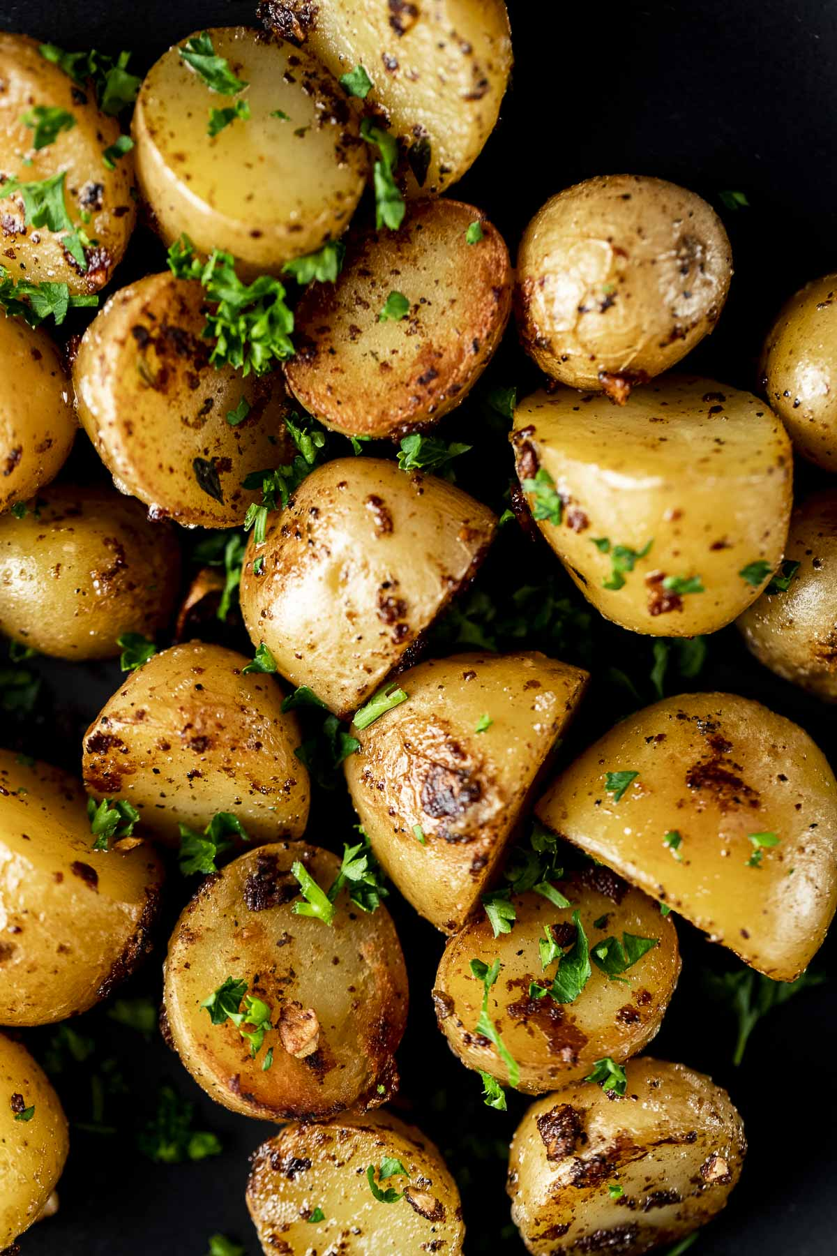 Overhead of mini sous vide potatoes on a plate with herbs sprinkled on top.