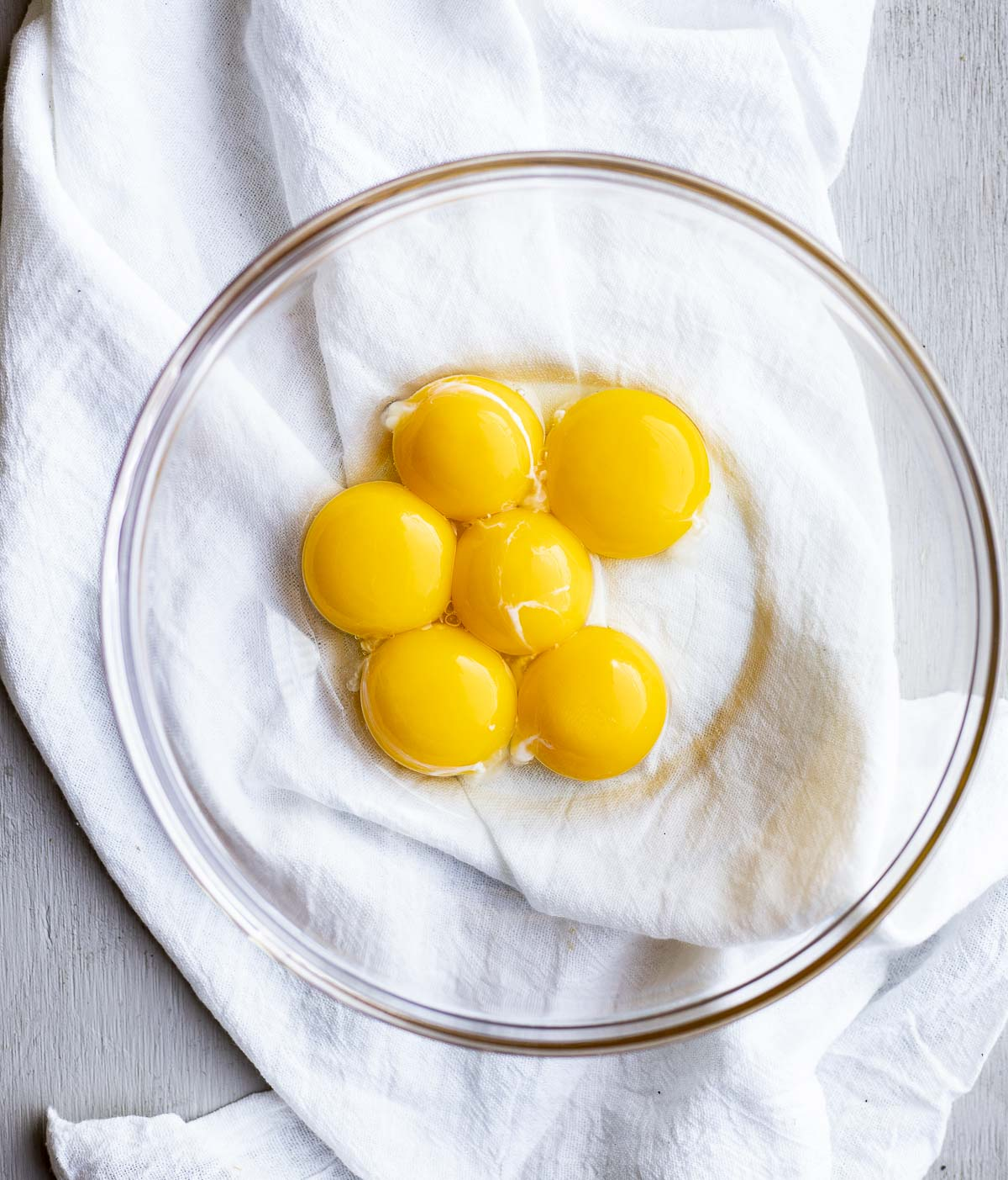 Six egg yolks in a glass bowl.