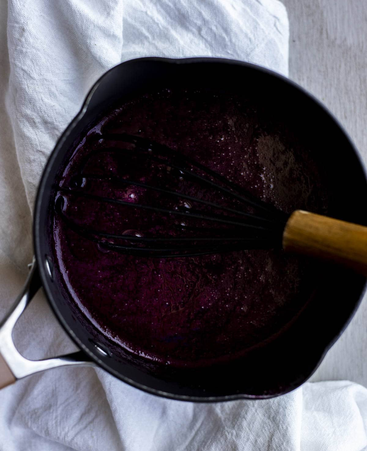 Overhead of blueberry curd being whisked in a sauce pan.