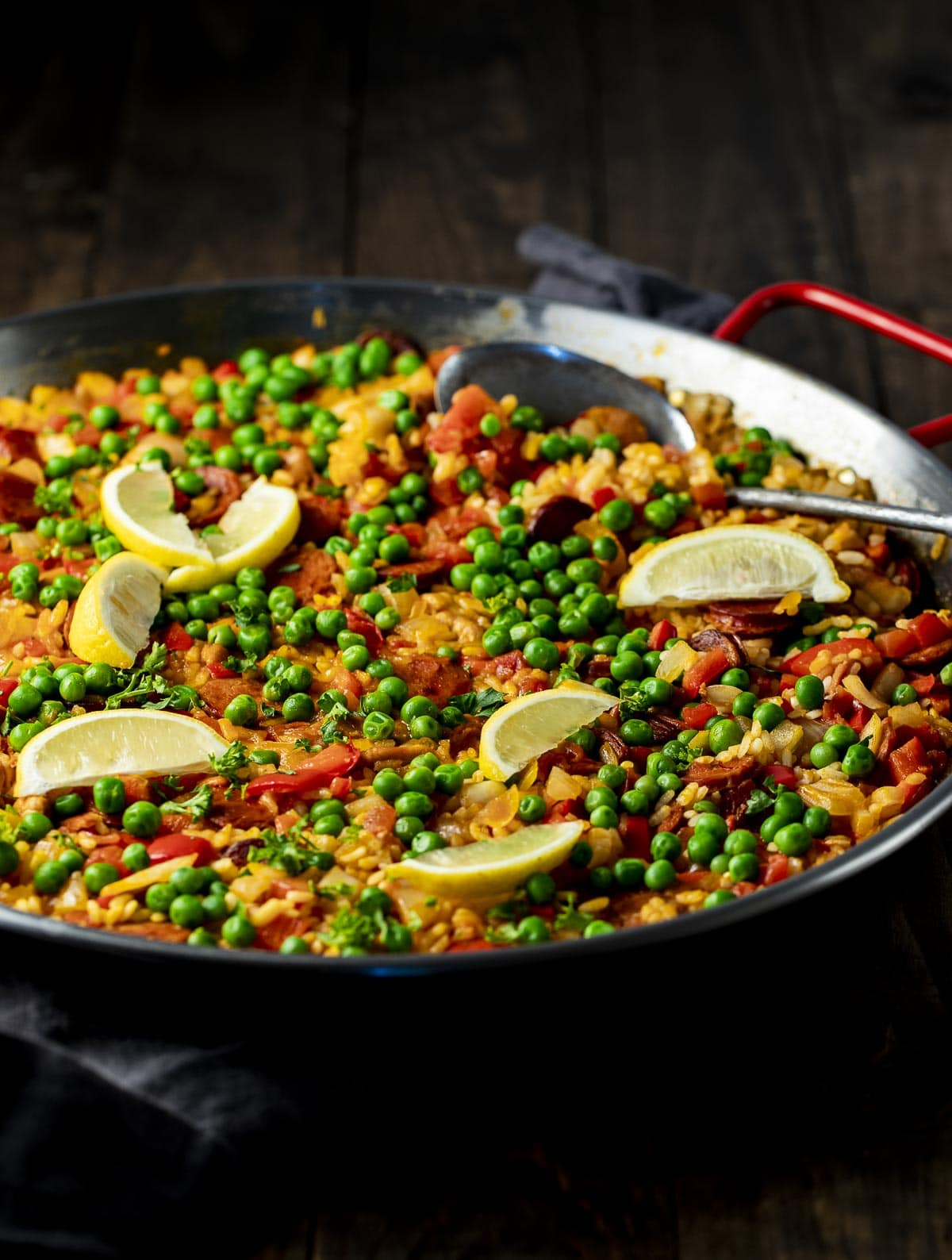 Side view of Spanish chicken and chorizo paella in a pan.