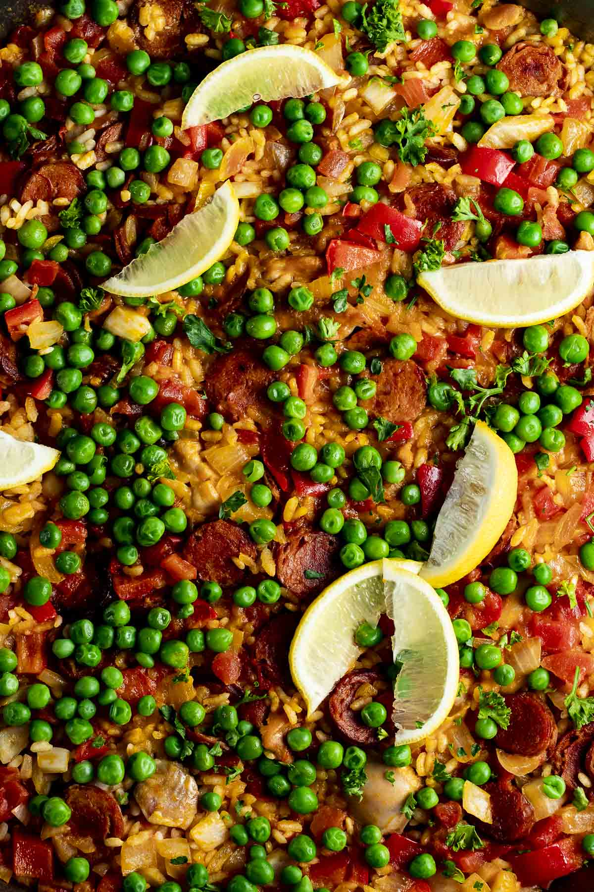 Close up of chicken and chorizo paella topped with peas and lemon slices.