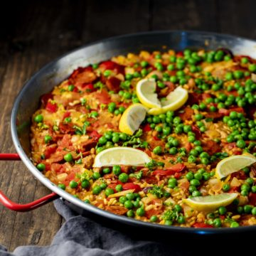 Side view of paella topped with green peas and lemon slices.